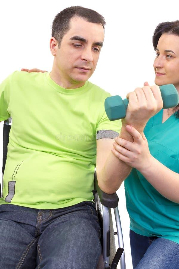O fisioterapeuta trabalha com o paciente em pesos de levantamento das mãos fotos de stock