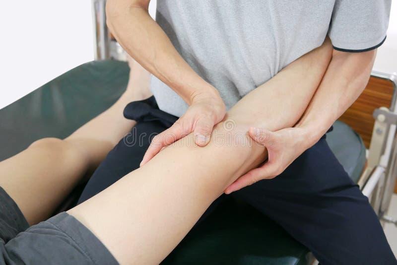 O fisioterapeuta trata o pé ao paciente para diminuir a dor e melhorar a mobilidade imagens de stock royalty free
