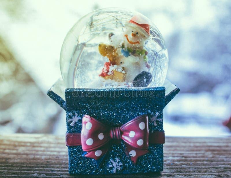 O floco de neve do presente do globo da neve do Natal com queda de neve e o boneco de neve brincam no fundo azul imagem de stock royalty free