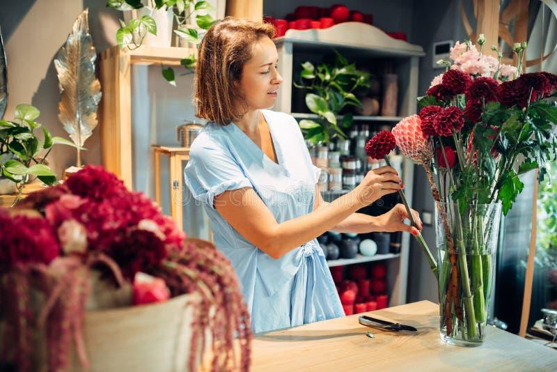 O florista fêmea põe flores em um vaso, loja floral fotografia de stock royalty free