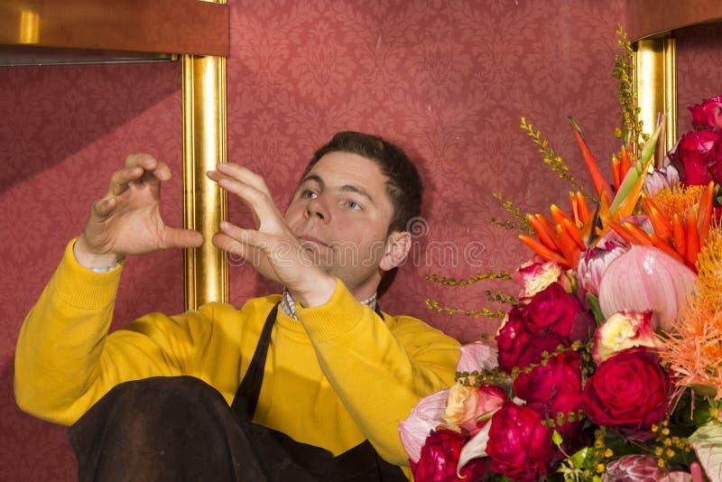 O florista pensa sobre o arranjo de flor na flor imagem de stock