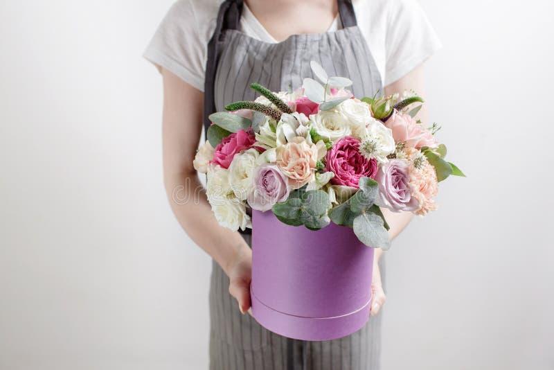 O florista recolhe o ramalhete guardando um grupo das mãos, caixa no primeiro plano Rosas cor-de-rosa e brancas fotos de stock