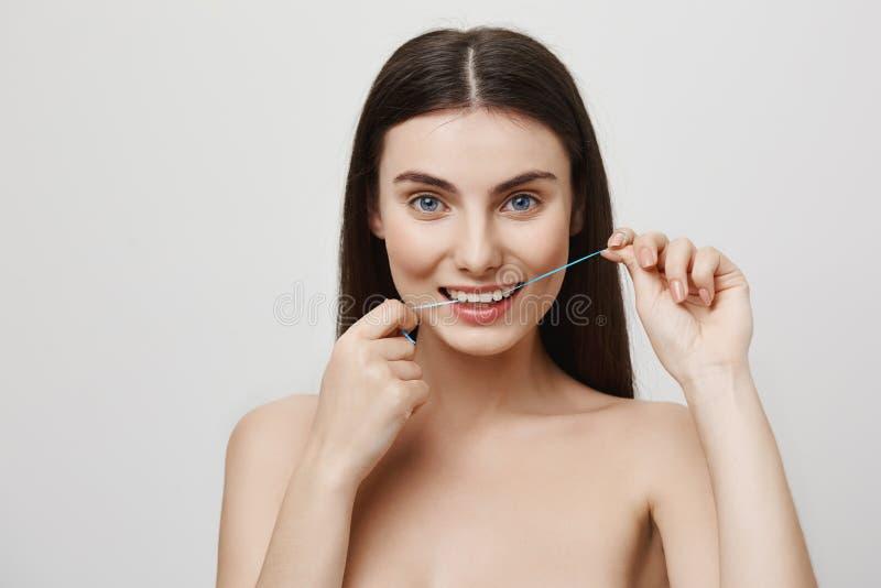 O Floss é importante para o cuidado do dente Tiro interno da mulher europeia atrativa com os olhos azuis que flossing os dentes,  imagem de stock
