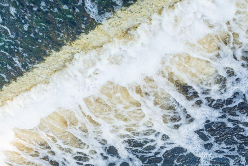 O fluxo rápido de um rio, um córrego da água azul de queda forma muitas espuma e bolhas imagem de stock