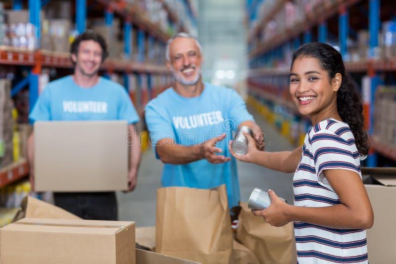 O foco da mulher feliz dá alguns bens aos voluntários fotos de stock royalty free