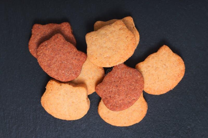 O foco do ponto do conceito do alimento fresco coze a forma orgânica caseiro do gato do tom das cookies de açúcar dois da manteig imagem de stock