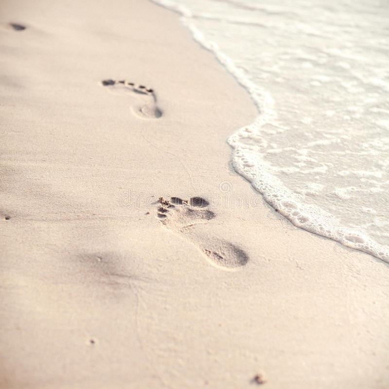 O foco e o tom macios das pegadas na praia tropical lixam a sagacidade imagem de stock royalty free