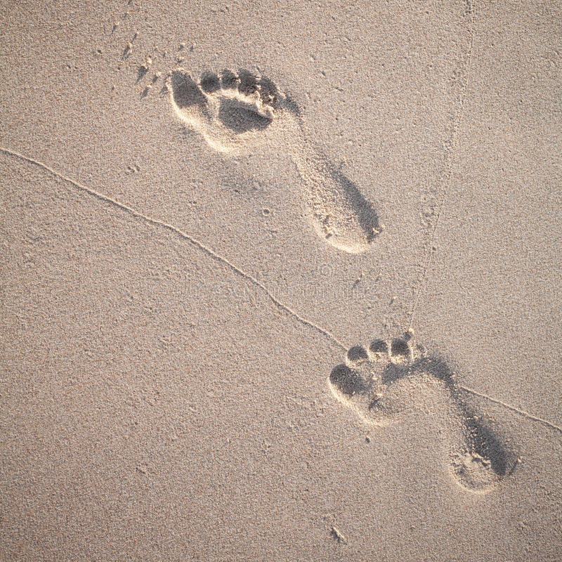O foco e o tom macios das pegadas na praia tropical lixam a sagacidade fotografia de stock