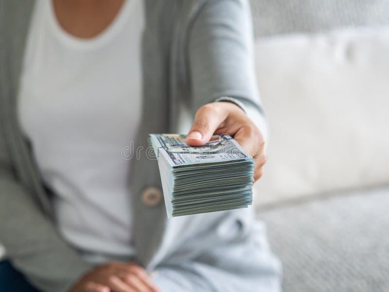 O foco macio na mulher entrega-lhe a proposição do dinheiro nós notas de dólar foto de stock royalty free
