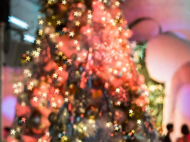 O foco obscuro na árvore de Natal vermelha com os decoros claros imagens de stock royalty free