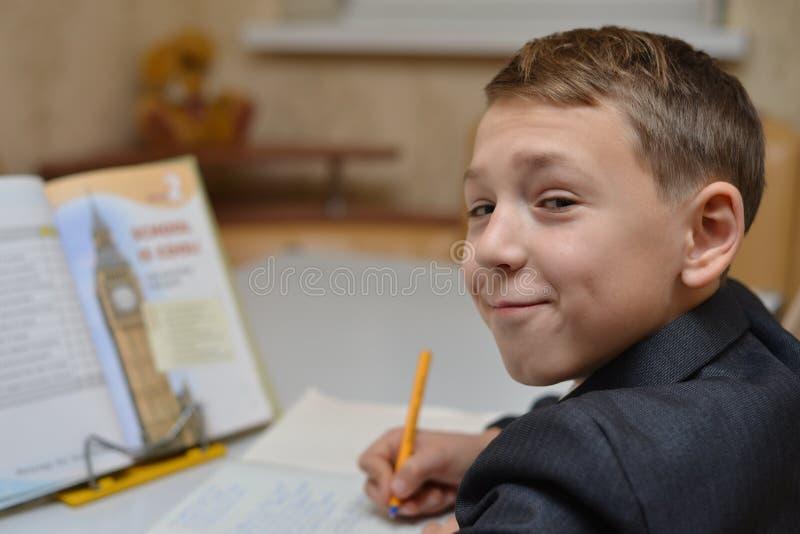 O foco seletivo do rapaz pequeno que aprende como escrever em casa seu nome, estudo da criança, crianças faz trabalhos de casa em imagens de stock