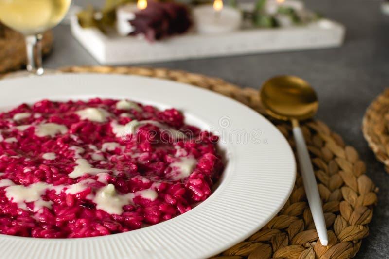O foco seletivo do risoto das beterrabas serviu com vidro do vinho branco, alimento italiano gourmet fotografia de stock royalty free