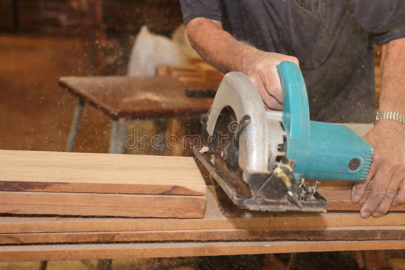 O foco seletivo nas mãos do carpinteiro superior que cortam uma parte de madeira com circular elétrica considerou na oficina da c imagem de stock
