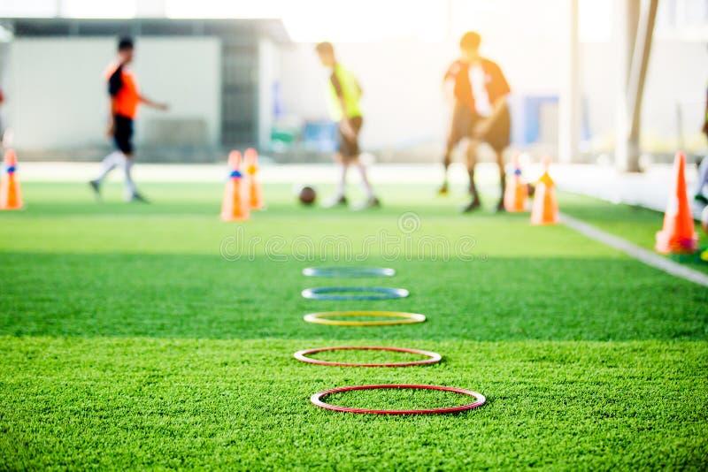 O foco seletivo para soar o marcador da escada e o cone são equipamento de treino do futebol no relvado artificial verde com os j fotos de stock royalty free