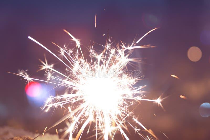 O fogo de Bengal sparkles na perspectiva das luzes da cidade, fotografia de stock