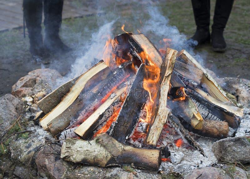 O fogo de madeira do acampamento, duas mulheres está olhando o fogo foto de stock