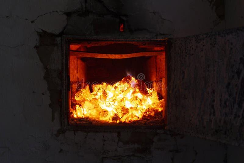 O fogo na fornalha Fim da brasa e do fogo acima Os carvões, chamas, calor, relaxam o fundo do conceito imagens de stock royalty free