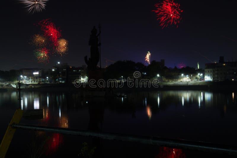O fogo trabalha na noite com opinião da cidade foto de stock royalty free