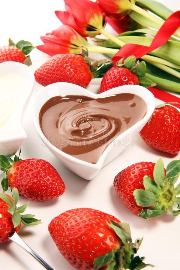 O fondue de Valentine Chocolate derreteu com morangos frescas e chocolate escuro e branco Tublips e corações do açúcar fotografia de stock
