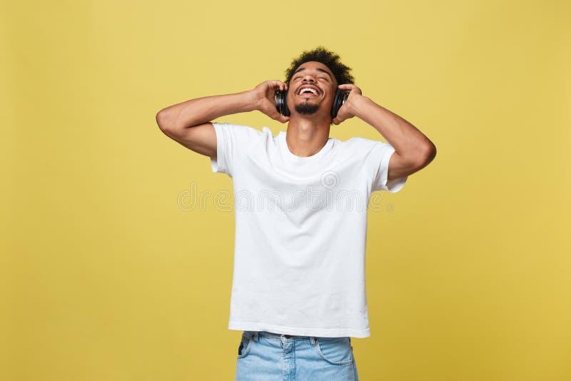 O fones de ouvido vestindo do homem afro-americano novo e aprecia a música sobre o fundo do ouro amarelo imagem de stock royalty free