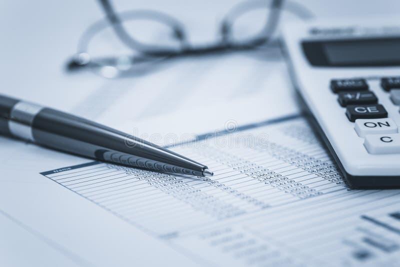 O forense financeiro explicando examina dados da planilha do estoque da conta bancária do banco com pena e calculadora dos vidros fotografia de stock