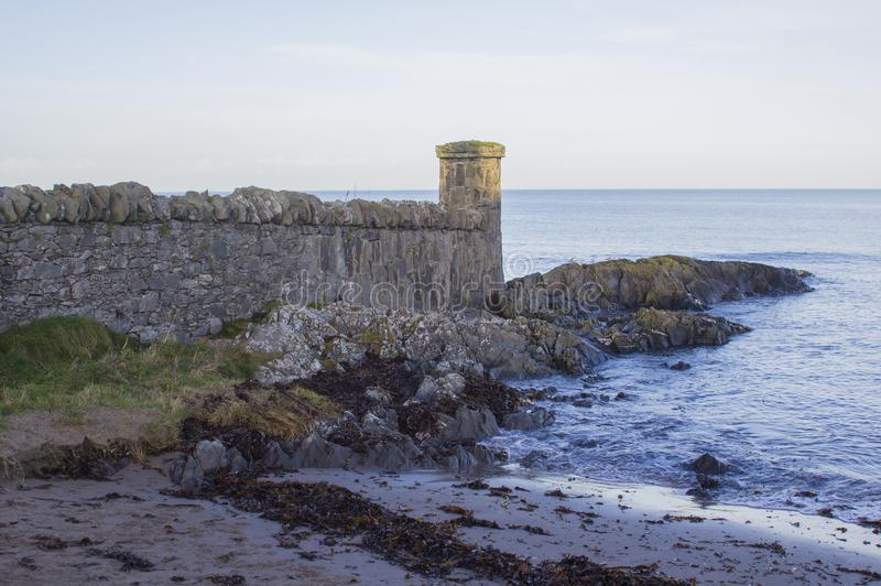 O foreshore rochoso e as fortificações construídas de pedra da réplica na vila de beira-mar de Groomsport na contagem para baixo  fotografia de stock