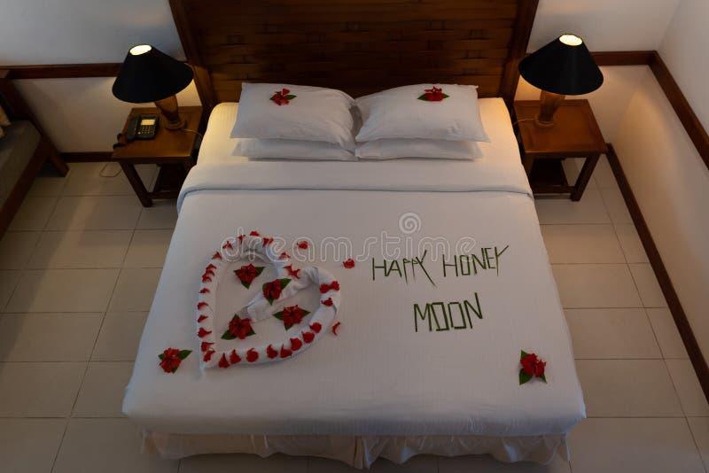 O formulário cremoso do descanso e do coração, assinatura do Valentim fez da flor cor-de-rosa vermelha na decoração da cama foto de stock royalty free