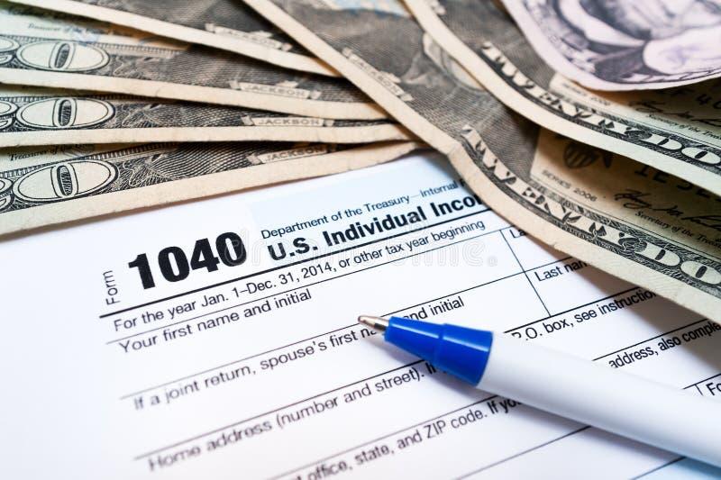 o formulário de declaração de rendimentos de 1040 indivíduos com bils do dinheiro da pena e do dólar fecha-se acima foto de stock royalty free