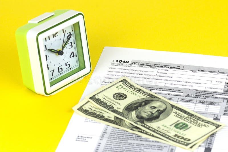 O formulário de imposto americano 1040 está na tabela Algumas contas estão na parte superior Dinheiro de 100 dólares e despertado imagem de stock royalty free