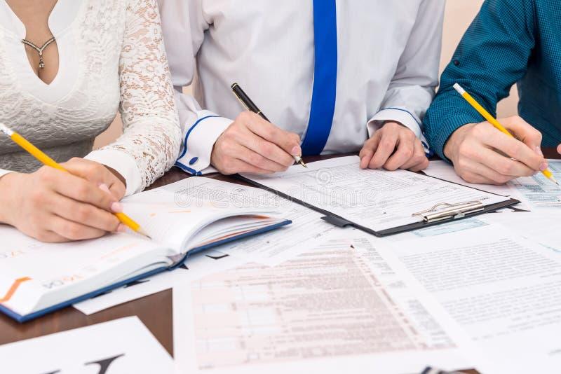 O formulário do enchimento 1040 com conselheiros ajuda no escritório imagens de stock royalty free