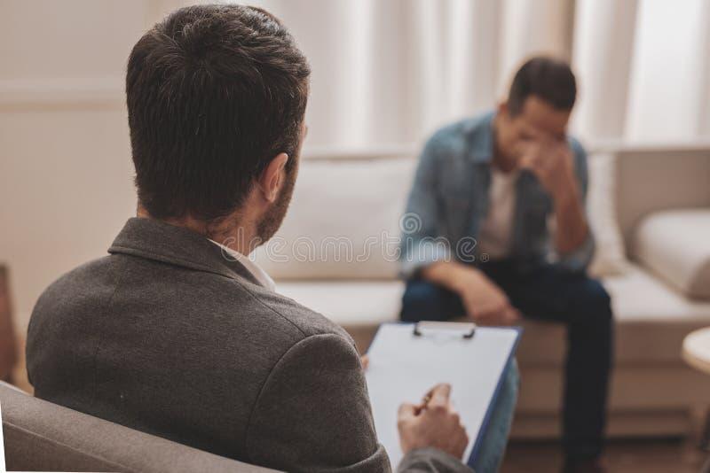 O fornecimento profissional do psicólogo ajuda seu cliente forçado imagem de stock