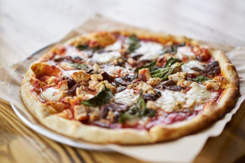 O forno autêntico do tijolo ateou fogo à pizza com queijo do ovalina e à galinha na tabela na pizaria fotos de stock royalty free