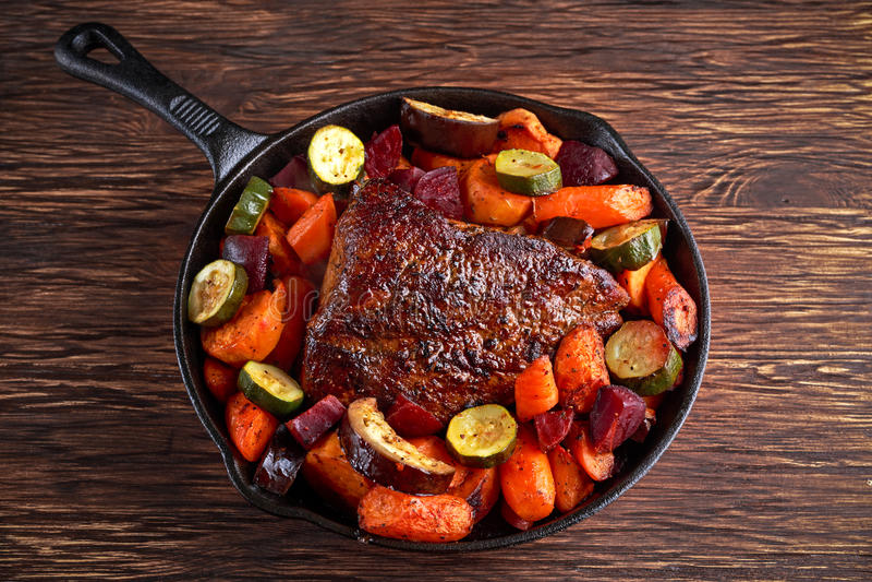 O forno cozeu o lombo de carne de porco suculento com os vegetais na bandeja rústica da chapa para assar foto de stock royalty free