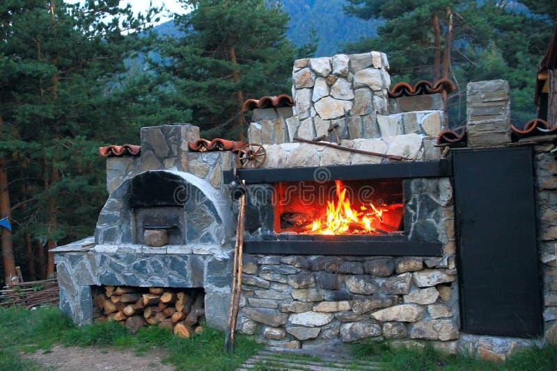 O forno do BBQ fez o _ do _ da pedra no pátio da casa imagens de stock