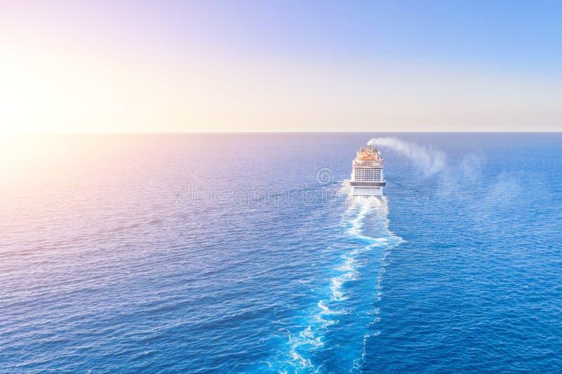 O forro do navio de cruzeiros entra no horizonte o mar azul que deixa uma pena na superfície do seascape da água durante o por do imagens de stock royalty free