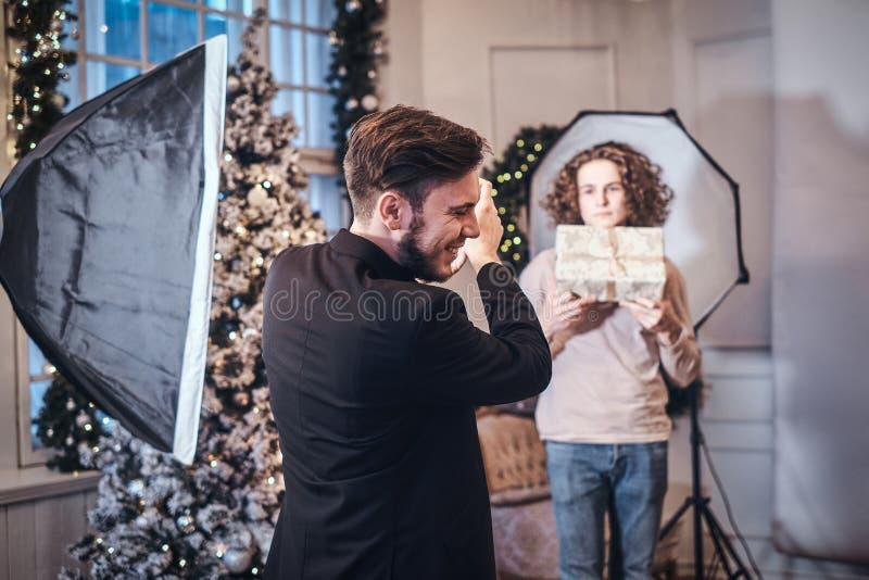 O fotógrafo alegre vestido em um traje elegante toma imagens de um indivíduo encaracolado com um presente foto de stock