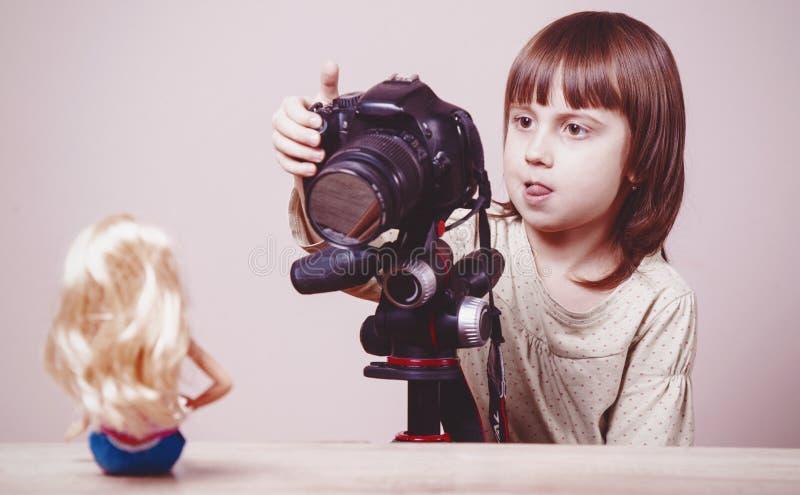 O fotógrafo bonito da menina da criança pequena está disparando em retratos da boneca no estúdio imagens de stock