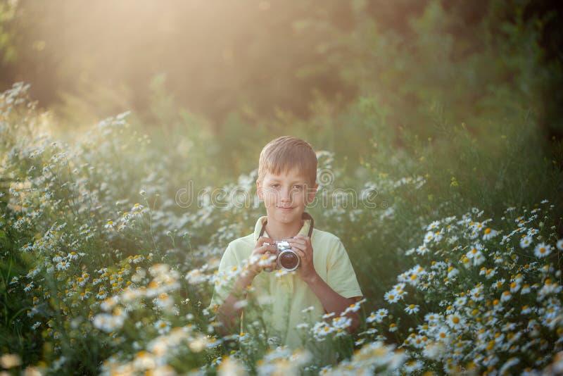 O fotógrafo bonito do menino dispara na câmera na natureza A criança toma uma foto no campo de flores da camomila foto de stock