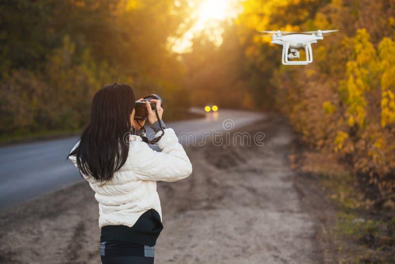 O fotógrafo da mulher dispara em um zangão de voo no parque do outono fotografia de stock royalty free