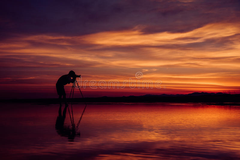 O fotógrafo da silhueta toma a foto o seascape bonito no por do sol fotos de stock royalty free