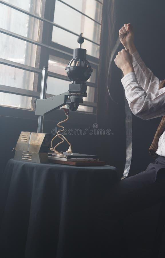 O fotógrafo do homem examina o filme na luz fotografia de stock royalty free
