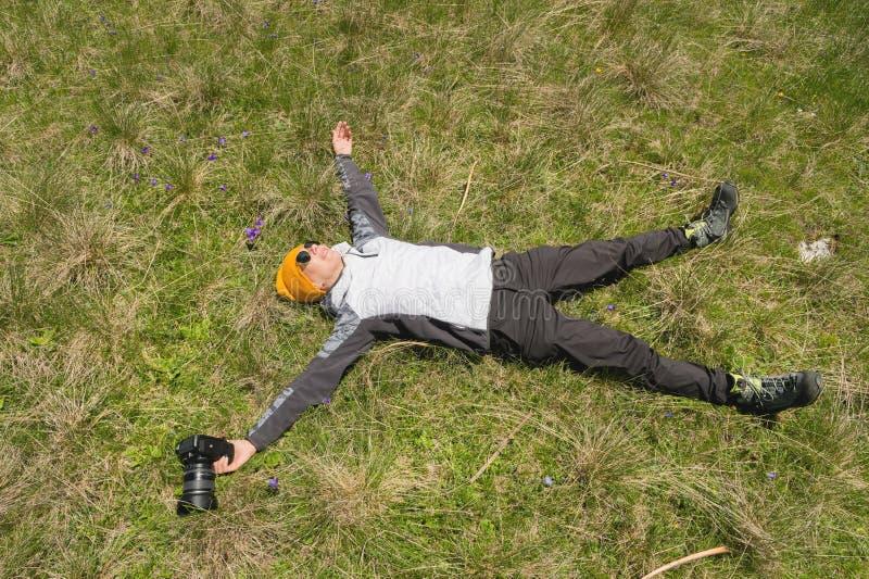 O fotógrafo feliz da menina nos óculos de sol e com uma câmera encontra-se à disposição nos braços e nos pés de espalhamento da g foto de stock