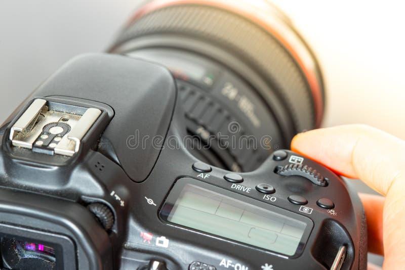 O fotógrafo guarda uma câmera de reflexo com a lente teleobjetiva em sua mão Tabela e portátil no fundo obscuro imagem de stock