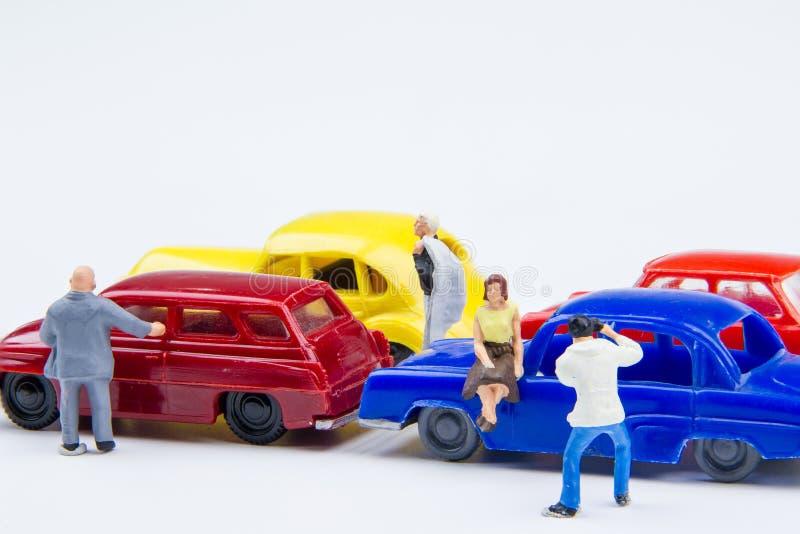 O fotógrafo minúsculo diminuto dos brinquedos toma a mulher das fotos que senta-se no Ca imagem de stock