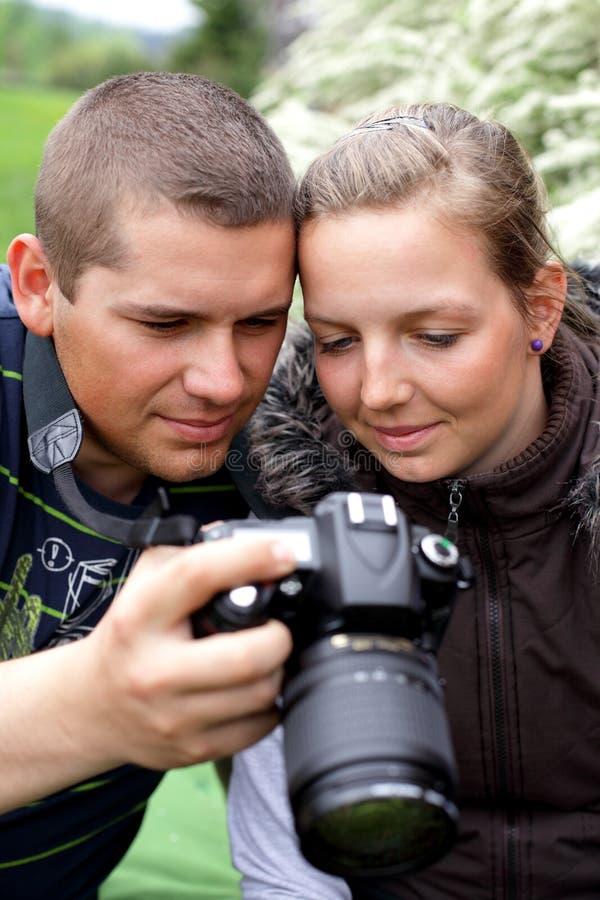 O fotógrafo mostra a menina do tiro da câmera imagens de stock royalty free