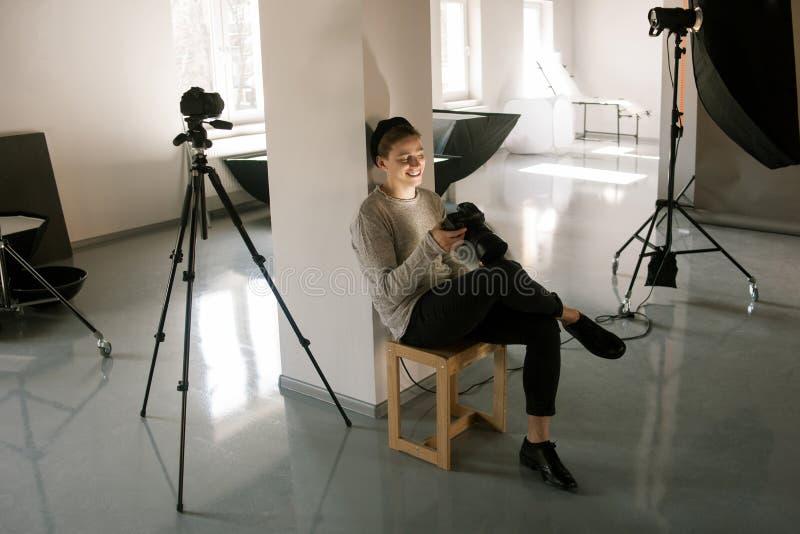 O fotógrafo no estúdio aprecia imagens na câmera imagem de stock