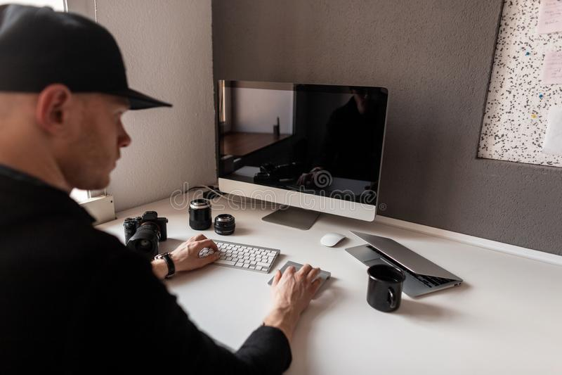 O fotógrafo novo à moda bem sucedido está trabalhando atrás de um computador em um escritório O homem no tampão senta-se em uma t fotos de stock
