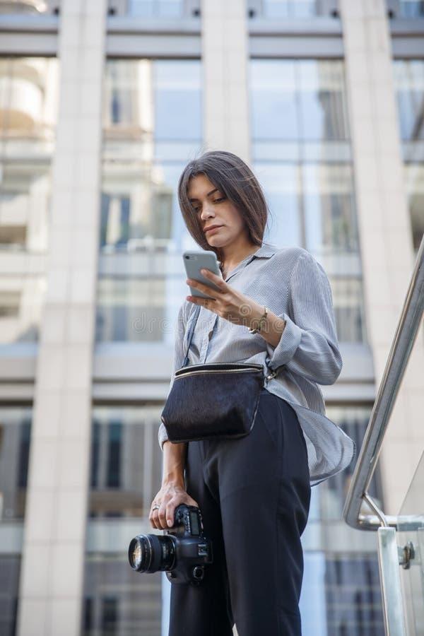 O fotógrafo novo está usando seu telefone ao guardar a câmera em seu assistente Construção urbana grande no fundo fotos de stock