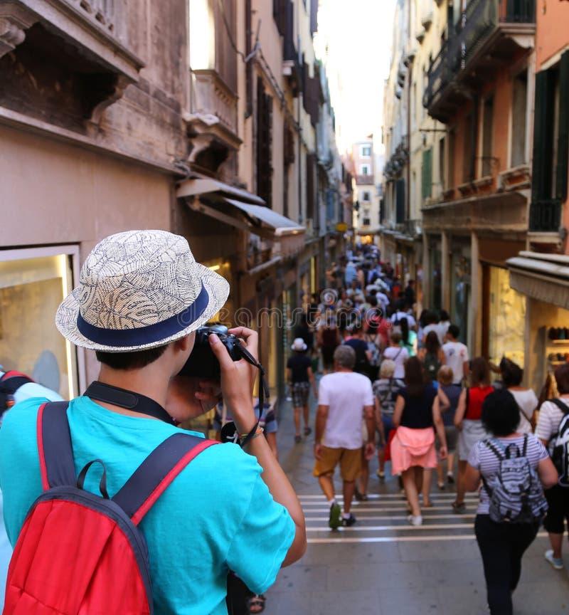 O fotógrafo novo toma uma imagem aos povos que andam no corvo foto de stock