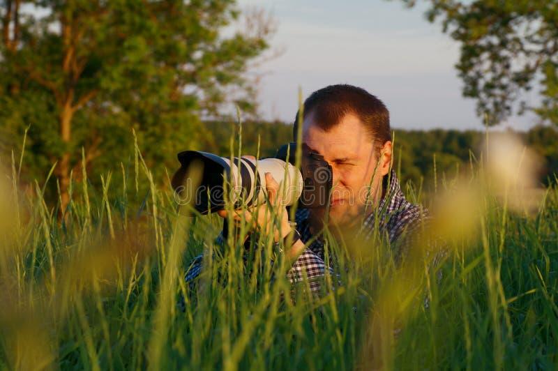 O fotógrafo olha a câmera fotografia de stock royalty free